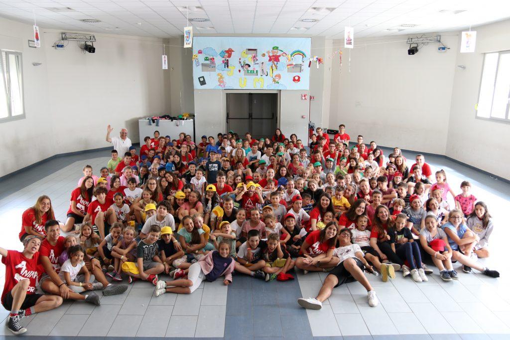 Foto di gruppo degli animatori in maglia rossa con i bambini del Grest 2018 in Auditorium - Iscrizioni grest 2019