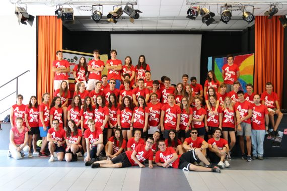 Foto di gruppo degli animatori in maglia rossa davanti al palco in auditorium