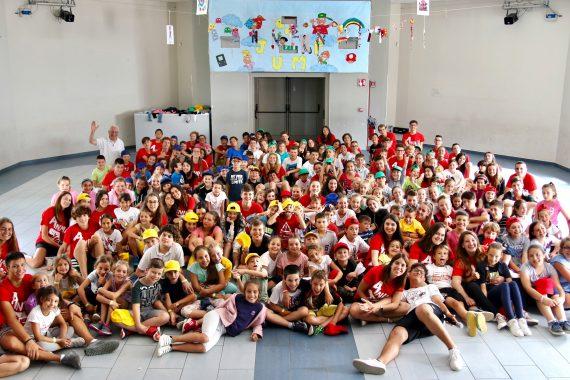 Foto di gruppo degli animatori in maglia rossa con i bambini del Grest 2018 in Auditorium